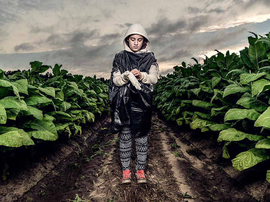 """A 16-year-old tobacco worker standing in a tobacco field in North Carolina wearing her work clothes. """"I don't feel any different in the fields than when I was 12,"""" she said. """"I [still] get headaches and … my stomach hurts. And like I feel nauseous…. I just feel like my stomach is like rumbling around. I feel like I'm gonna throw up."""""""