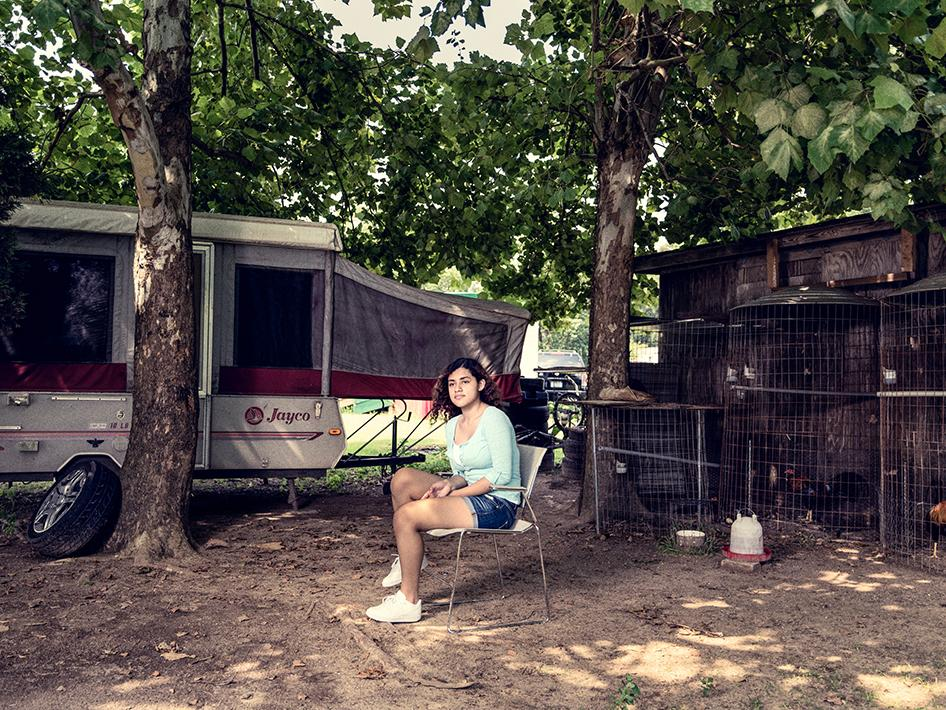 """A 16-year-old tobacco worker in North Carolina outside the mobile home where she lives with her mother, three sisters, two brothers, and nephew in North Carolina. Since she turned 12, she has spent her school summer vacations working as a hired laborer on tobacco farms to help support her family. """"With the money that I earn, I help my mom. I give her gas money. I buy food from the tobacco [work] for us to eat,"""" she said. """"Then I try to save up the money so I can have my school supplies and school stuff like clothes and shoes."""""""