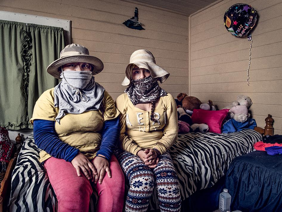 """""""Sara"""" (left) and """"Susana,"""" 16-year-old twin sisters who worked together on tobacco farms in 2015, sit in their bedroom in the clothes they wear to try to protect themselves in tobacco fields. They described working near areas where pesticides were being applied. Susana said, """"We are just working … and the worker is on the tractor spraying almost very close to us. But they don't take us out of that area. They don't even warn us that it is dangerous. Nothing. We are just working and we cover ourselves well because the smell is very strong, and we get sick with the smell of that spray."""" Sara said, """"I feel dizzy, very dizzy because the smell is unbearable. It's very strong and my stomach begins to feel stirred. I feel as if I am going to faint right then and there from the smell."""""""