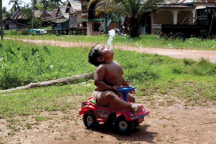 Addict: two-year-old Aldi Suganda Rizal smokes a cigarette at his family home in Indonesia.